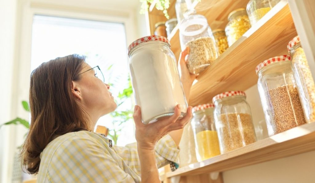 woman in the pantry holding a jar of flour