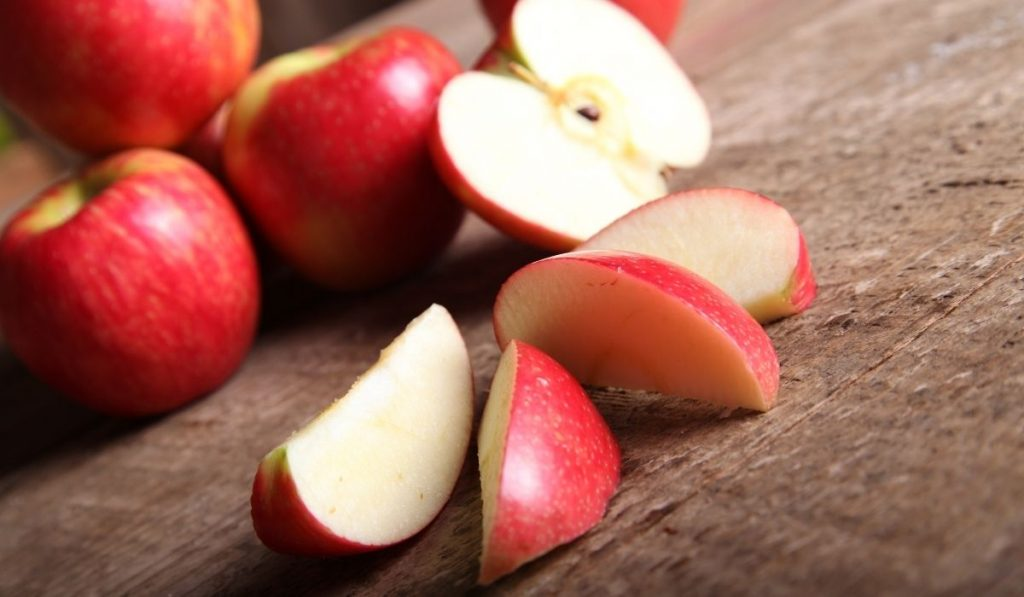 whole and sliced apples on a wooden table