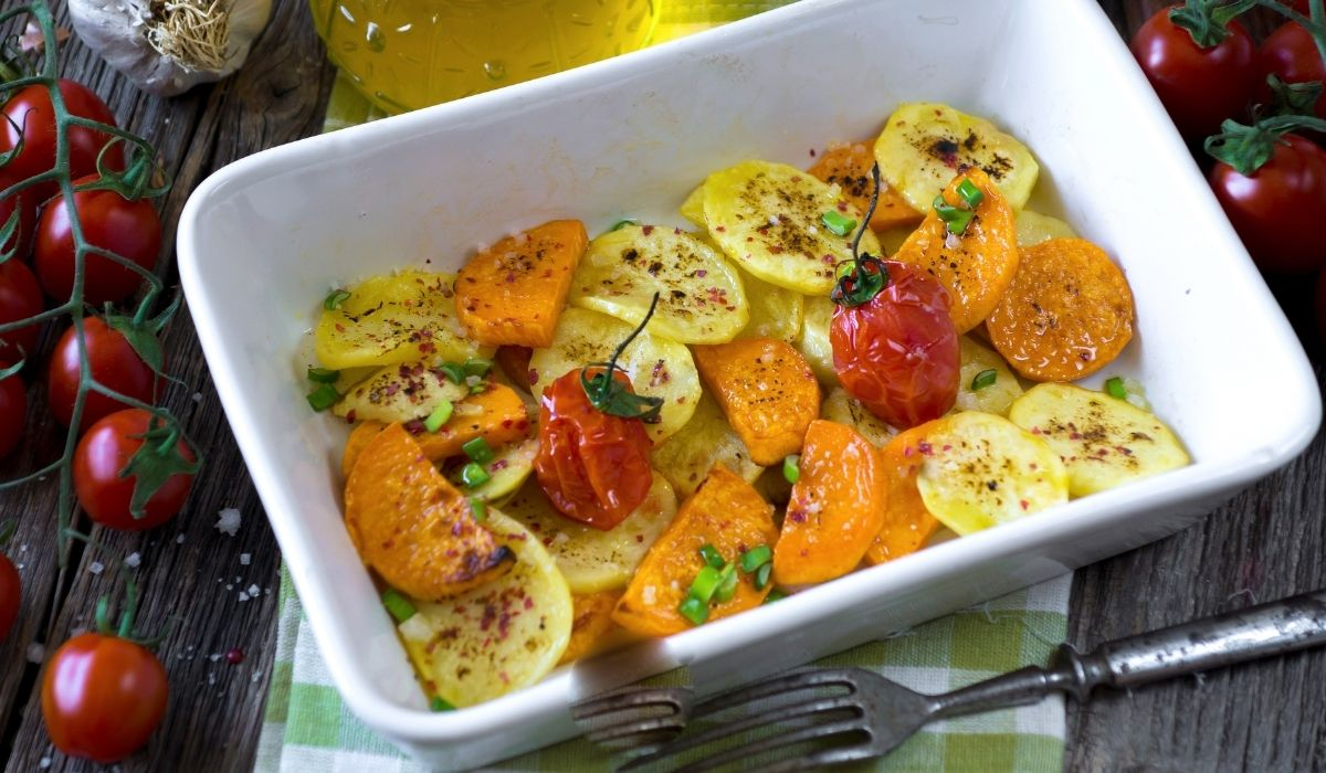 roasted potatoes and sweet potatoes in a white ceramic with fresh cherry tomatoes in the background