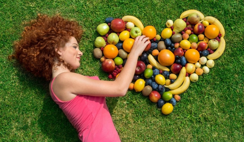 woman resting on grass with mixed fruits formed in heart
